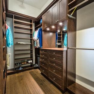Diseño de armario vestidor unisex, marinero, de tamaño medio, con armarios con paneles empotrados, puertas de armario de madera en tonos medios y suelo de madera en tonos medios