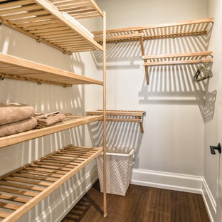 This is an example of a mid-sized beach style gender-neutral walk-in wardrobe in Miami with medium hardwood floors and light wood cabinets.