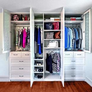 Foto de armario unisex, clásico renovado, con armarios con paneles empotrados, puertas de armario blancas y suelo de madera en tonos medios