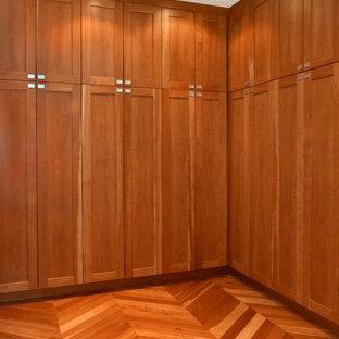 Foto de armario unisex, clásico, de tamaño medio, con armarios con paneles lisos, puertas de armario de madera oscura, suelo de madera en tonos medios y suelo marrón