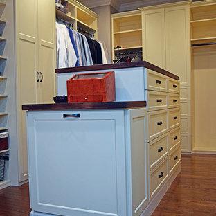 Ejemplo de armario vestidor unisex, clásico, grande, con armarios estilo shaker, suelo de madera en tonos medios y puertas de armario beige