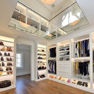 Inspiration for a contemporary gender-neutral walk-in wardrobe in Other with shaker cabinets, white cabinets, medium hardwood floors and brown floor.