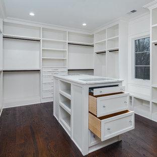 Exemple d'un grand dressing chic neutre avec un placard à porte shaker, des portes de placard blanches, un sol en bois foncé et un sol marron.