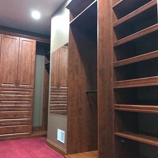 Imagen de armario vestidor unisex, tradicional, grande, con armarios con paneles con relieve, puertas de armario de madera en tonos medios, moqueta y suelo rojo