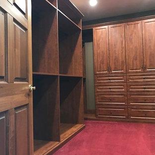 Foto på ett stort vintage walk-in-closet för könsneutrala, med luckor med upphöjd panel, skåp i mörkt trä, heltäckningsmatta och rött golv