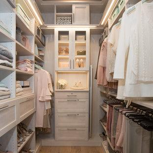 Ejemplo de armario vestidor de mujer, minimalista, de tamaño medio, con armarios estilo shaker, puertas de armario grises, suelo de madera clara y suelo beige