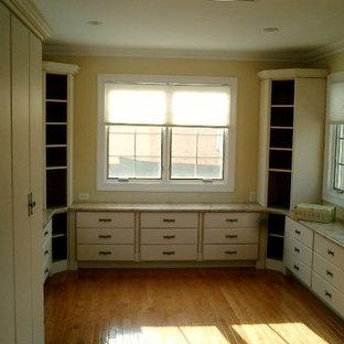 Immagine di una grande cabina armadio unisex classica con ante bianche e pavimento in legno massello medio