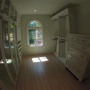 Foto de vestidor de hombre, de estilo americano, de tamaño medio, con armarios con paneles empotrados, puertas de armario blancas, suelo de madera clara y suelo beige