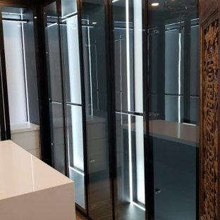 Foto de armario y vestidor unisex, minimalista, de tamaño medio, con armarios tipo vitrina, puertas de armario negras, suelo de madera clara y suelo marrón