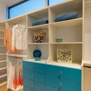 Foto de armario vestidor de mujer, tradicional renovado, de tamaño medio, con armarios con paneles lisos, puertas de armario azules, suelo de madera clara y suelo marrón