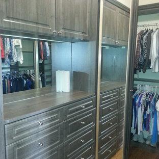Ejemplo de armario vestidor unisex, clásico renovado, grande, con armarios con paneles con relieve, puertas de armario grises y suelo de madera clara