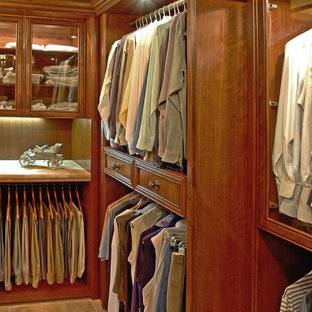 Photo of a mid-sized traditional gender-neutral walk-in wardrobe in Other with recessed-panel cabinets, medium wood cabinets and travertine floors.