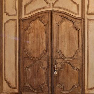 Modelo de armario de mujer, rural, pequeño, con suelo de madera en tonos medios, suelo marrón, armarios con paneles con relieve y puertas de armario con efecto envejecido