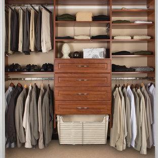 Ejemplo de armario vestidor de hombre, tradicional renovado, de tamaño medio, con armarios con paneles empotrados, puertas de armario de madera oscura, moqueta y suelo beige