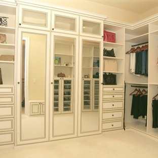 Photo of a large traditional women's walk-in wardrobe in Tampa with recessed-panel cabinets, white cabinets and carpet.