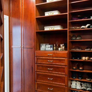 Large elegant men's walk-in closet photo in Los Angeles with medium tone wood cabinets and shaker cabinets