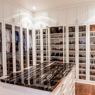 Réalisation d'un dressing design neutre avec un placard à porte vitrée, des portes de placard blanches, un sol en bois brun et un sol marron.