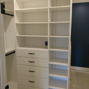 Foto de armario vestidor unisex, actual, pequeño, con armarios abiertos, puertas de armario blancas, suelo de cemento y suelo marrón