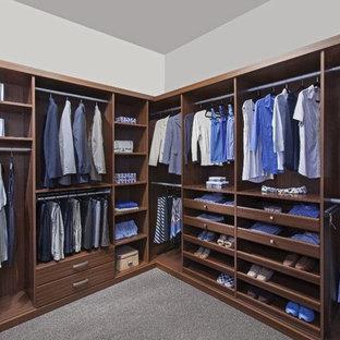 Ejemplo de armario vestidor de hombre, clásico renovado, grande, con armarios abiertos, puertas de armario de madera oscura, moqueta y suelo gris