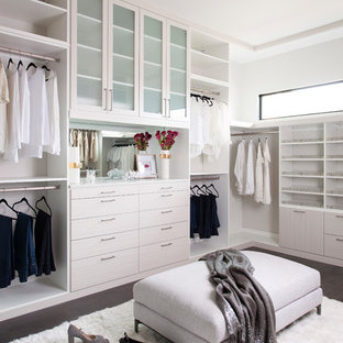 Imagen de armario vestidor de mujer, extra grande, con armarios estilo shaker, puertas de armario blancas, suelo de madera oscura y suelo marrón