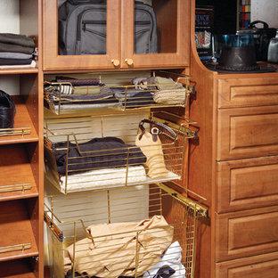 Foto di una cabina armadio per uomo chic di medie dimensioni con ante con bugna sagomata, ante in legno bruno e moquette