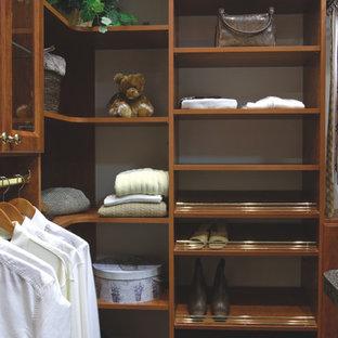 Diseño de armario vestidor de hombre, clásico, de tamaño medio, con armarios abiertos, puertas de armario de madera en tonos medios, moqueta y suelo verde