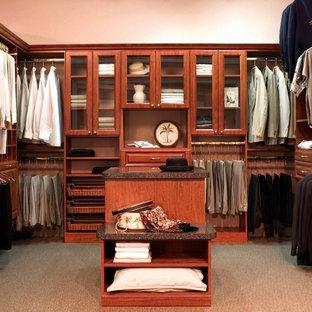 Ejemplo de armario vestidor unisex, costero, de tamaño medio, con armarios con paneles con relieve, puertas de armario de madera en tonos medios, moqueta y suelo marrón