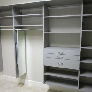 Ejemplo de armario vestidor unisex, actual, de tamaño medio, con armarios abiertos, puertas de armario grises, suelo de baldosas de porcelana y suelo gris