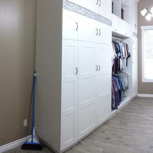 Idées déco pour un grand dressing room moderne neutre avec un placard à porte shaker, des portes de placard blanches, un sol en vinyl et un sol marron.