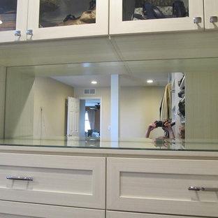 Imagen de armario vestidor grande con armarios tipo vitrina y suelo de madera oscura