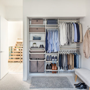 Réalisation d'un petit placard dressing minimaliste neutre avec moquette, un sol gris, un placard sans porte et des portes de placard blanches.