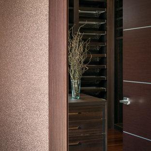 Foto de armario vestidor unisex, actual, grande, con armarios con paneles lisos, puertas de armario de madera en tonos medios y suelo de bambú
