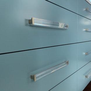 Modelo de armario vestidor papel pintado, de tamaño medio, con armarios con paneles lisos, puertas de armario azules, papel pintado y moqueta