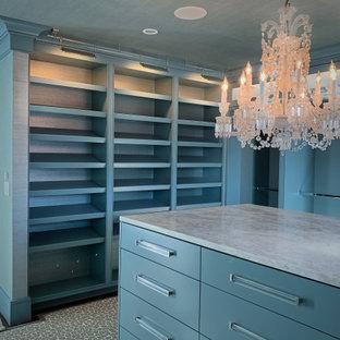 Ejemplo de armario vestidor papel pintado, de tamaño medio, con armarios con paneles lisos, puertas de armario azules, moqueta y papel pintado