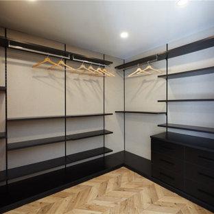 Diseño de armario y vestidor unisex y casetón, de tamaño medio, con armarios abiertos, puertas de armario negras, suelo de corcho y suelo multicolor