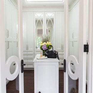 Aménagement d'un grand dressing room classique pour une femme avec des portes de placard blanches, un sol en bois foncé, un sol marron et un placard avec porte à panneau encastré.