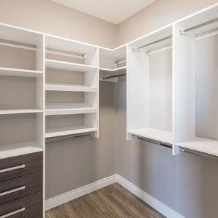 Diseño de armario vestidor unisex, clásico renovado, pequeño, con armarios con paneles lisos, puertas de armario de madera oscura y suelo laminado