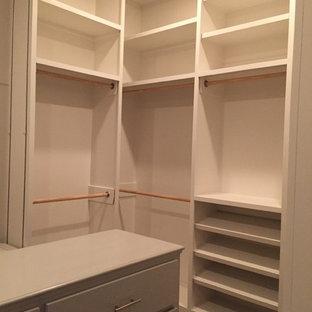 Ejemplo de armario vestidor rural con armarios con paneles lisos, puertas de armario grises y suelo de madera clara