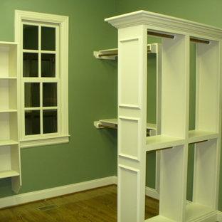 Immagine di una cabina armadio unisex chic di medie dimensioni con ante lisce, ante bianche e parquet chiaro
