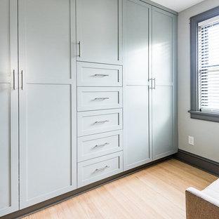 Diseño de armario moderno, de tamaño medio, con armarios estilo shaker, puertas de armario azules, suelo de madera clara y suelo marrón