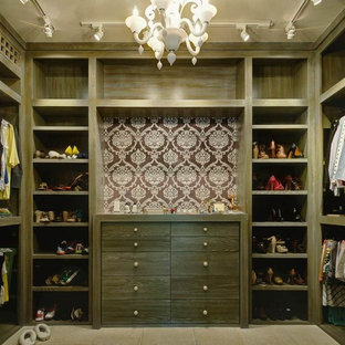 Design ideas for a mid-sized contemporary women's walk-in wardrobe in Houston with flat-panel cabinets, distressed cabinets and limestone floors.