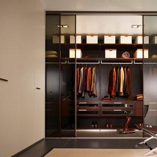 Cette image montre un dressing minimaliste de taille moyenne et neutre avec un placard à porte vitrée, des portes de placard en bois sombre et un sol en carrelage de porcelaine.