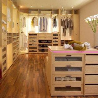 Idee per una grande cabina armadio unisex design con ante di vetro, ante in legno chiaro e moquette