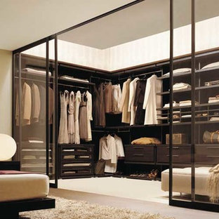Design ideas for a large contemporary gender-neutral walk-in wardrobe in Dallas with dark wood cabinets and carpet.