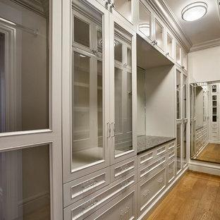 Inredning av ett klassiskt stort walk-in-closet för könsneutrala, med luckor med infälld panel, grå skåp och ljust trägolv
