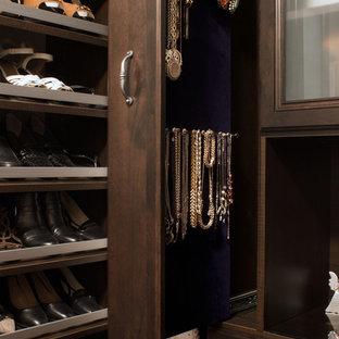 Esempio di una piccola cabina armadio per donna classica con ante con bugna sagomata, ante in legno bruno e parquet scuro