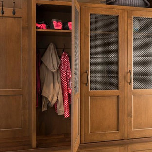 Inspiration for a medium sized classic gender neutral standard wardrobe in Houston with beaded cabinets, medium wood cabinets and terracotta flooring.