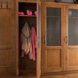 Idée de décoration pour un placard dressing tradition de taille moyenne et neutre avec un placard à porte affleurante, des portes de placard en bois brun et un sol en carreau de terre cuite.