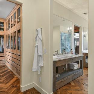 Diseño de armario y vestidor unisex, de estilo de casa de campo, grande, con armarios tipo vitrina, puertas de armario de madera clara y suelo de madera en tonos medios