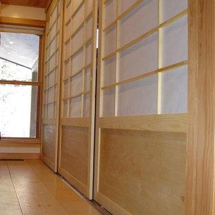 Diseño de armario unisex, de estilo zen, de tamaño medio, con armarios con paneles empotrados, puertas de armario de madera clara y suelo de madera clara
